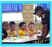 A police officer speaks with school children